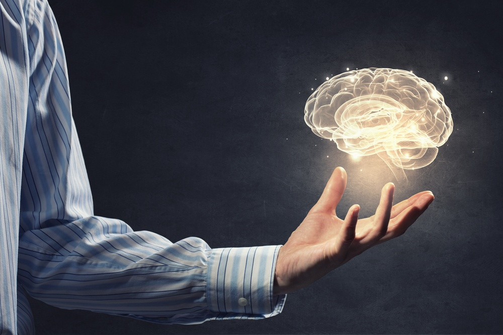 Close up of businessman holding digital image of brain in palm.jpeg